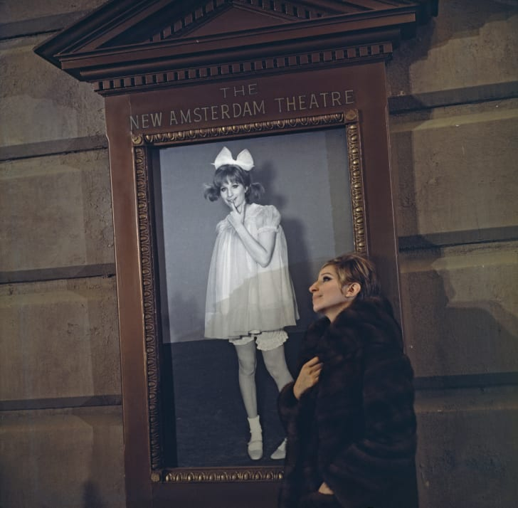 Barbra Streisand next to her Funny Girl poster.