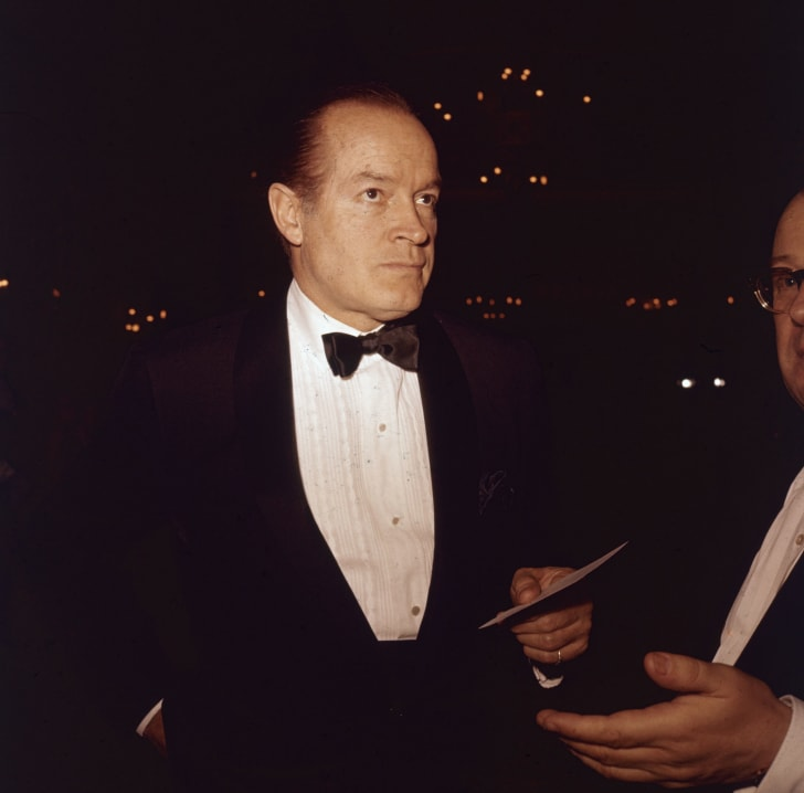 October 1961: American movie icon Bob Hope (1903 - 2003) arrives at a social function wearing a jacket and bow tie