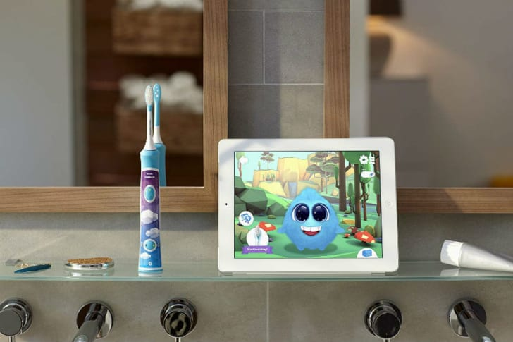The Philips Sonicare for Kids electric toothbrush sits next to a display that features the brushing app