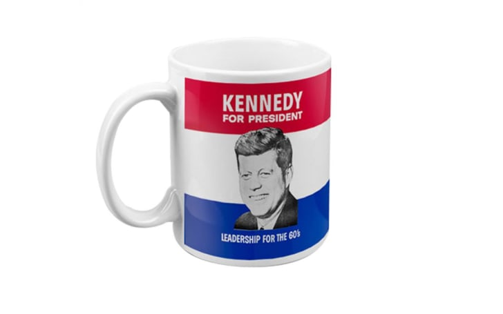 A 'Kennedy for President' mug with a black-and-white picture of John F. Kennedy on it