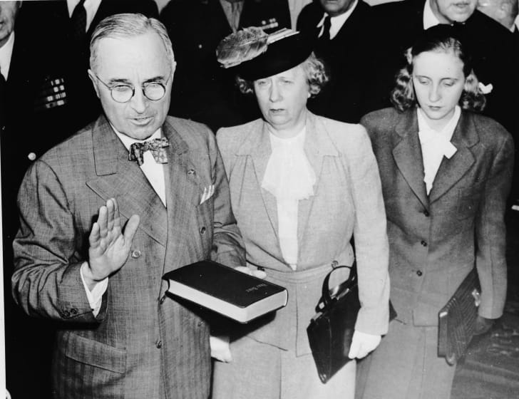 Harry Truman takes the oath of office in 1945; standing beside him are his wife, Bess, and daughter, Margaret.