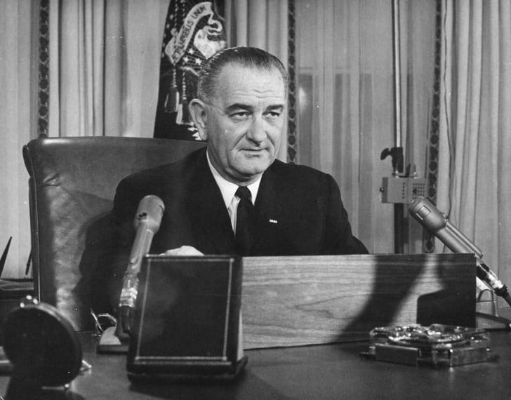 Lyndon B. Johnson behind a podium.