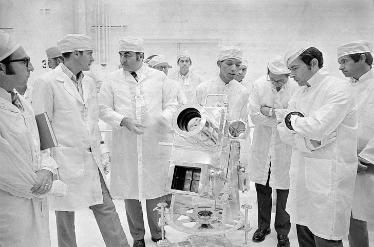 George Carruthers surrounded by other scientists looking at the Lunar Surface Ultraviolet Camera