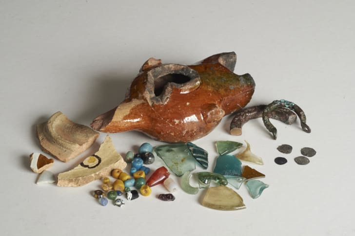 A selection of excavated finds from Essouk-Tadmekka, including fragments of glazed ceramics, stone beads, a cowrie shell, a fragment of silk textile, a carved stone torso, and vessel glass fragments.