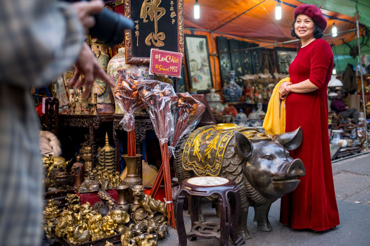 Market-goers pose for photos with bronze pig statues at Hang Luoc street Lunar New Year fair, a favorite shopping place for local people in Hanoi, Vietnam.
