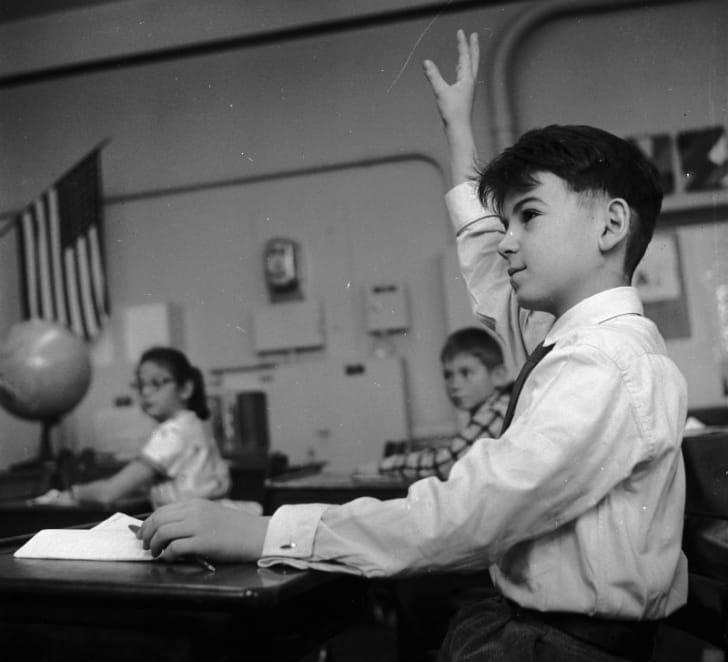 A child raises his hand in class circa the 1950s