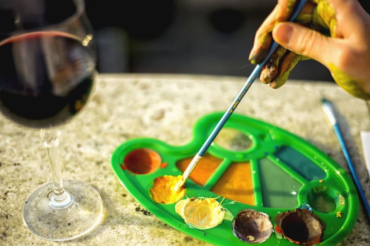 A painter dips a brush into a palette that sits next to a glass of red wine