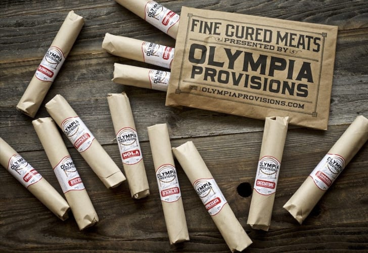 An assortment of salami near an Olympia Provisions label
