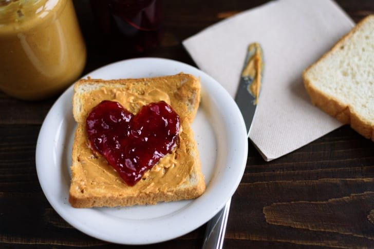 A piece of bread spread with peanut butter and jelly in a heart shape
