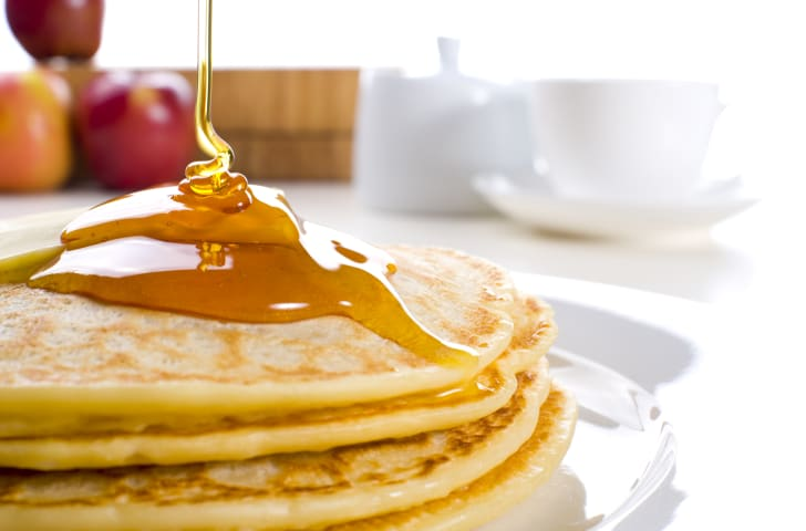 Drizzling syrup over pancakes