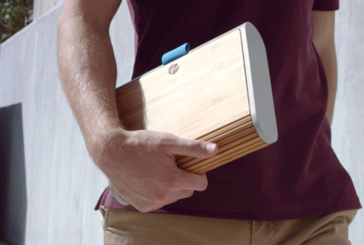Person holding wooden lunch box