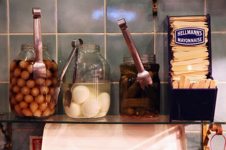 Jar of pickled eggs on bar shelf.