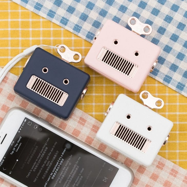 Three robot-shaped Bluetooth speakers next to an iPhone