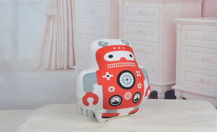 A robot-shaped pillow on a bed