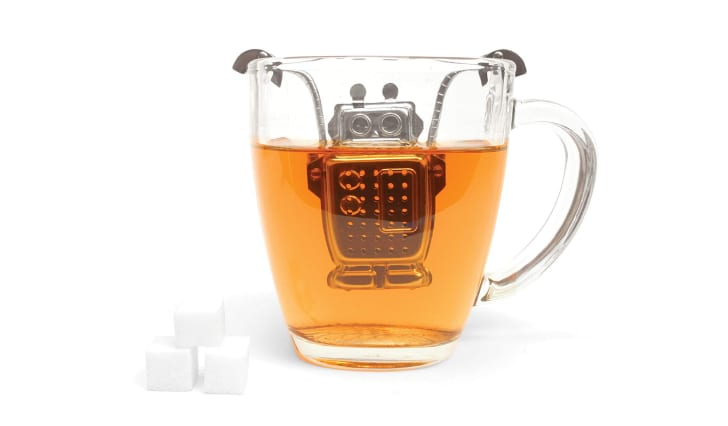 A robot-shaped tea infuser resting inside a glass mug full of tea