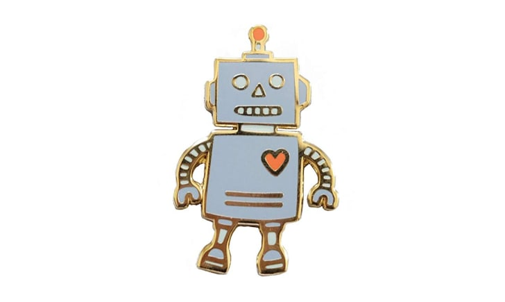 A gray enamel pin in the shape of a robot
