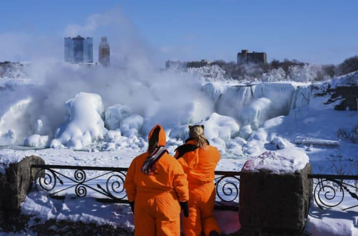 Visitors observe frozen areas of Niagara Falls in 2015