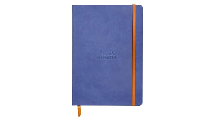 A periwinkle blue notebook with an orange elastic band