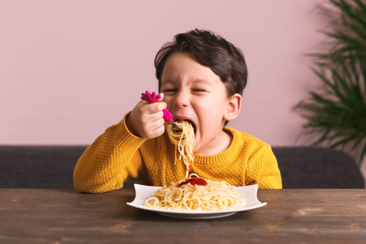Young boy eats a plate of spaghetti