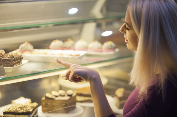 Woman picks out a dessert in a bakery