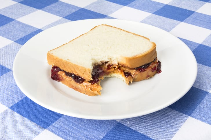 A peanut butter and jelly sandwich on a plate atop a blue and white checked tablecloth