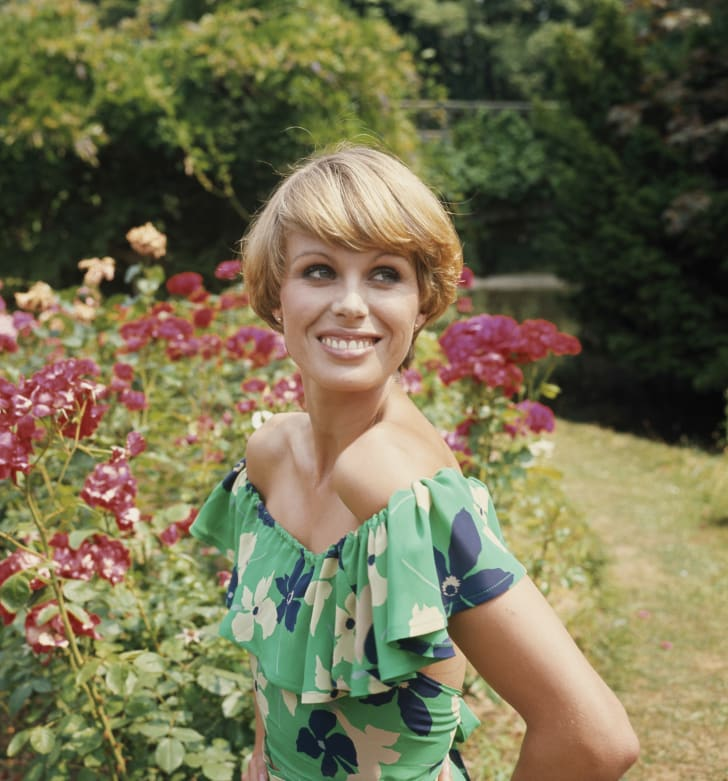 Joanna Lumley, British actress, wearing a floral print dress while posing in a garden at Pinewood Studios during filming of 'The New Avengers', in Iver Heath, Buckinghamshire, England, Great Britain, 12 July 1976
