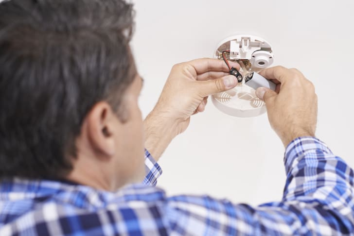 Man replaces battery in home's smoke detector