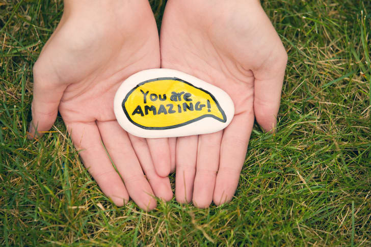 Person holding a rock that says 'You are amazing!'