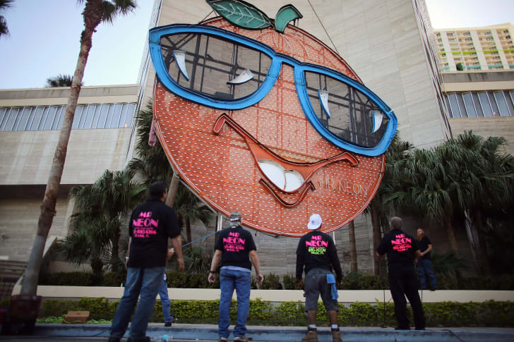 Workers watch as the Big Orange, a New Year's time ball, is prepared to be raised onto the side of the Hotel InterContinental