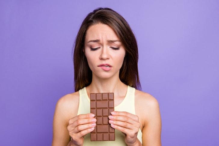 Young woman resisting chocolate bar