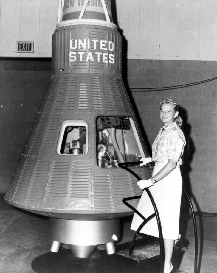 Jerrie Cobb poses next to a Mercury spaceship capsule