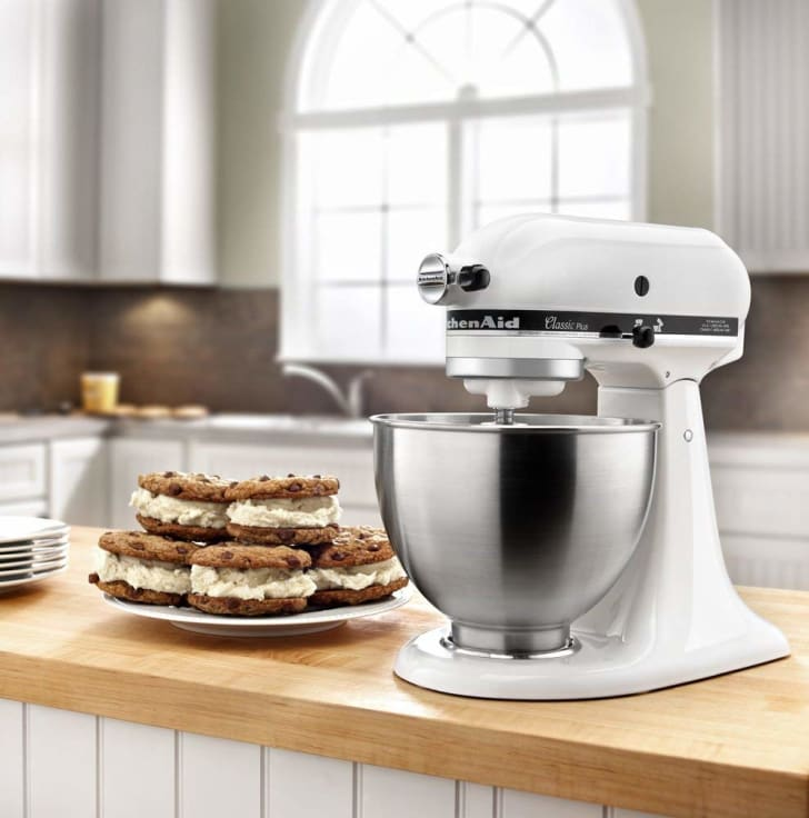 A white KitchenAid stand mixer on a kitchen island next to a plate of whoopie pies