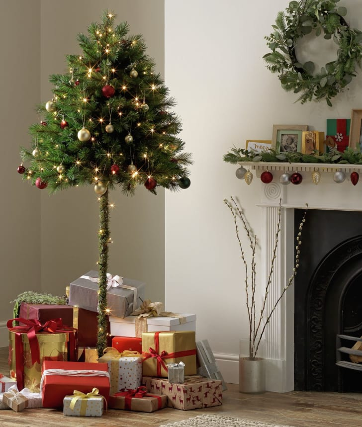 An Argos half tree in a living room with presents underneath it