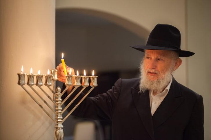 rabbi lighting a menorah