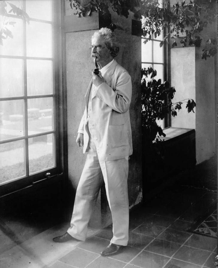Mark Twain standing near a window while wearing a white suit and smoking a pipe
