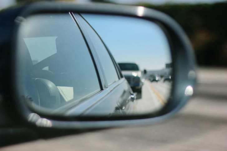 A car is seen in a rearview mirror