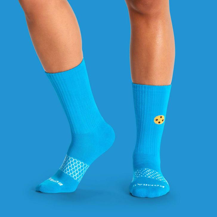 A pair of legs wearing Cookie Monster socks