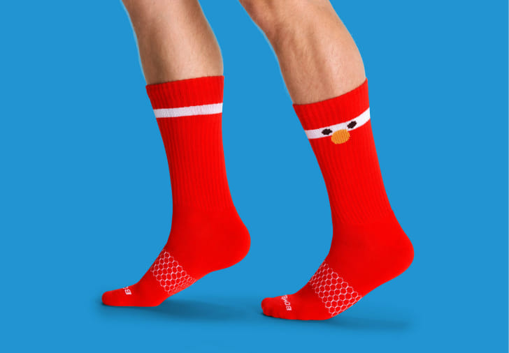 A man's legs showing off red Elmo socks
