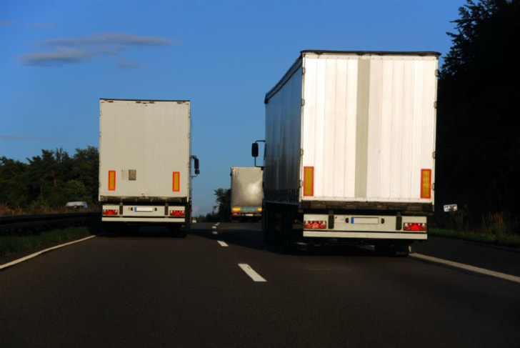 Commercial trucks take up both lanes of a road