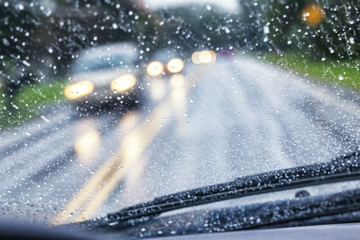 Heavy rain falls on a car windshield