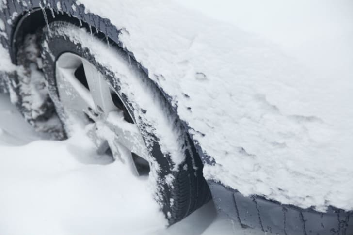 A car tire is stuck in snow