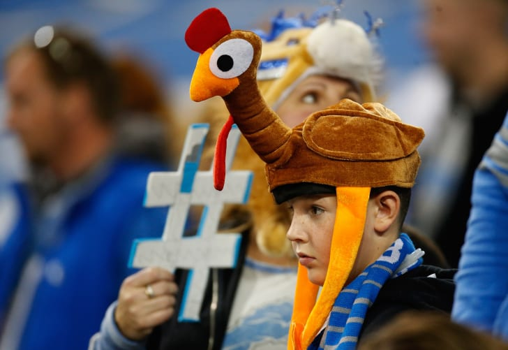 A kid wears a turkey hat to a Thanksgiving day football game.