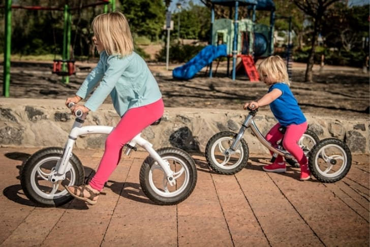Two girls on bikes outdoors