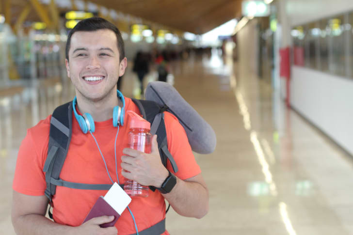 A man holds a water bottle at the airport