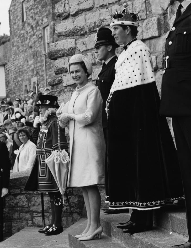 Prince Charles wearing a crown and a blue and ermine cape as he is invested as the Prince of Wales, with Queen Elizabeth II at Caernarvon Castle, Wales, July 1, 1969.