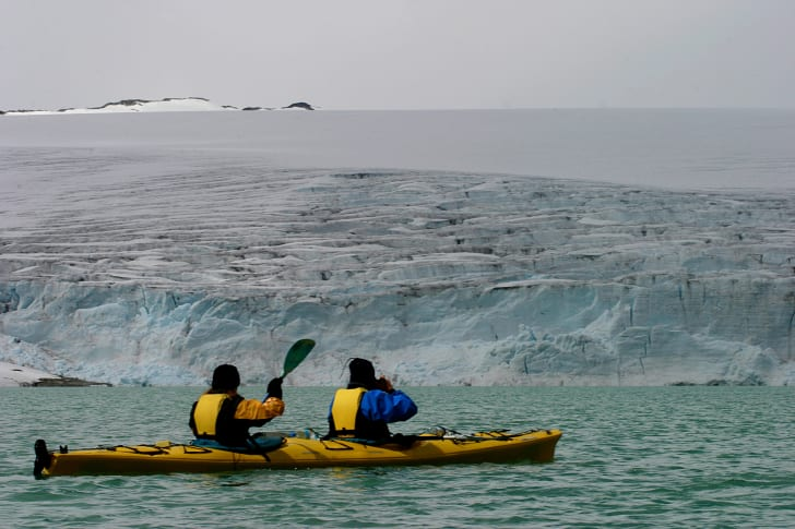 Two people kayak near glaciers