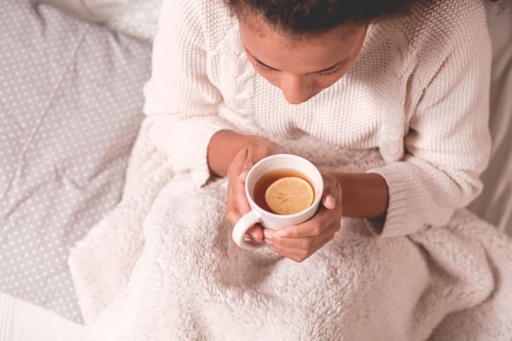 Woman in a sweater holding a cup of tea