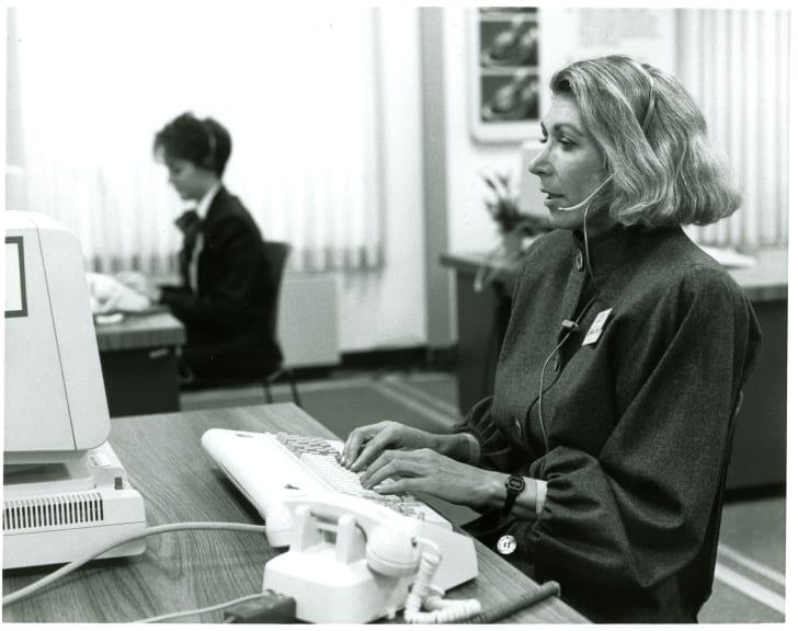 Two talk-line hosts are shown answering calls at their desks in 1988