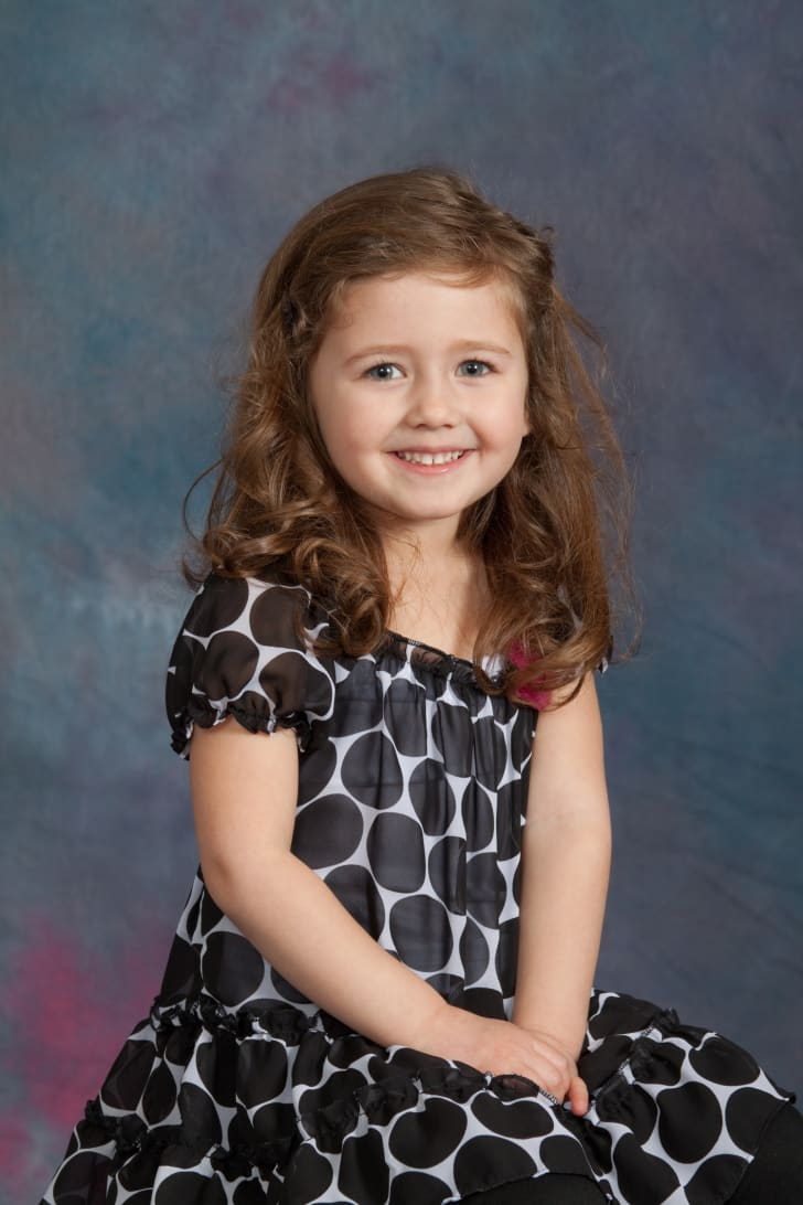 A little girl in a yearbook portrait photo