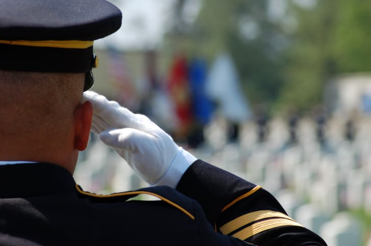 Soldier saluting in uniform in cemetery.